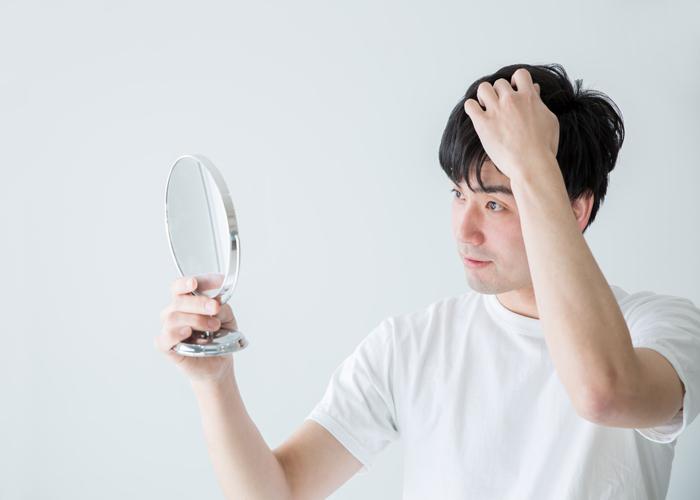 髪の毛を確認する男性