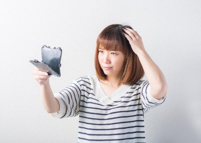 自分の頭頂部を鏡で見る女性